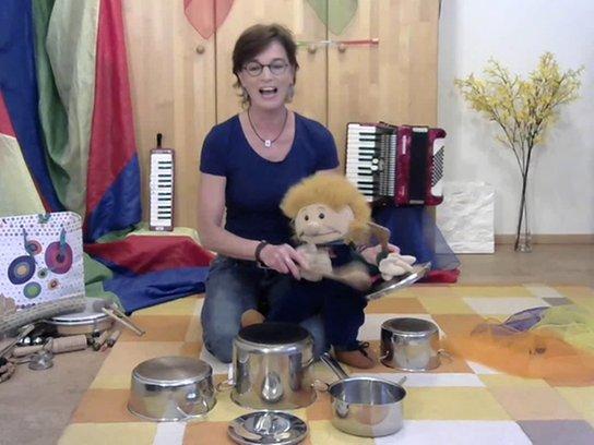Christiane Becker sitzt mit Friedolin inmitten ihrer vielseitigen Instrumente